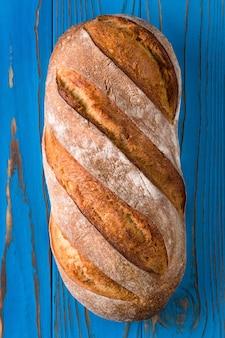 Świeży pieczony chleb żytni na niebieskim tle drewnianych.