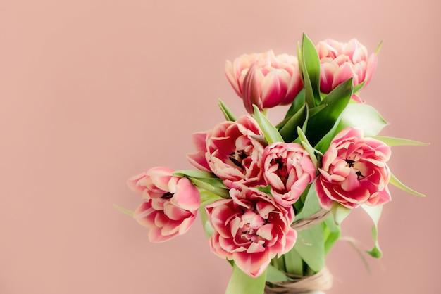 Świeży piękny różowy tulipanowy bukiet na różowym tle. kartka wielkanocna. skopiuj miejsce