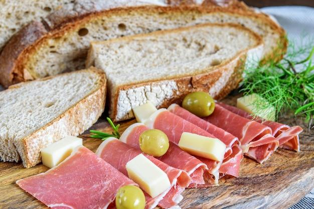 Świeży pokrojony jamon serrano zbliżenie. zintegrowany domowy chleb, ser i oliwki do przekąsek na drewnie.