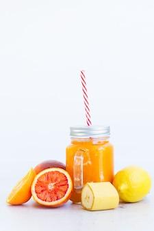 Świeży pomarańczowy napój smoothy w szklanych słoikach ze składnikami