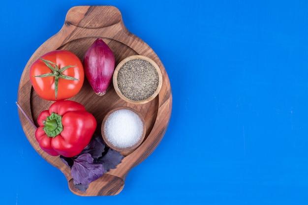 Świeży pomidor, cebula i czerwona papryka na desce.
