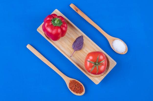 Świeży pomidor, czosnek i czerwona papryka na drewnianym talerzu z przyprawami.