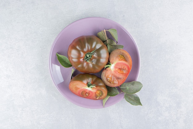 Świeży pomidor w talerzu na marmurowej powierzchni