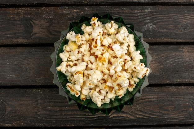 Świeży popcorn widok z góry wewnątrz okrągłego talerza na brązowym