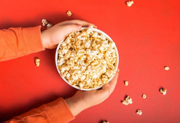 Świeży popcorn wylał się z miski na czerwono