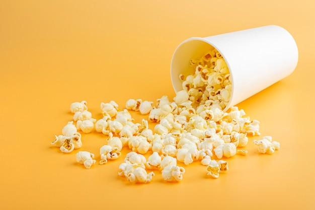 Świeży popcorn wysypał się z białego pudełka na pomarańczowym tle. koncepcja przekąski w kinie. jedzenie do oglądania filmu i rozrywki z bliska. mocap z pudełkiem na popcorn