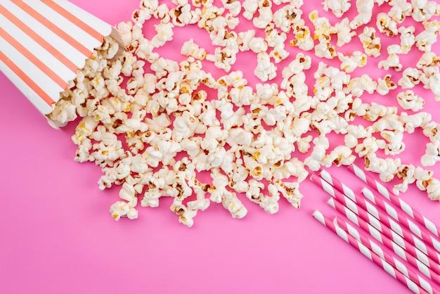 Świeży popcorn z góry rozłożony na różowej, filmowej przekąsce kukurydzianej