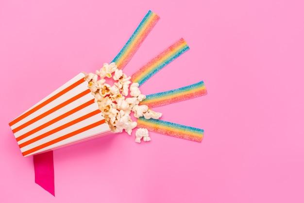 Świeży popcorn z widokiem z góry w papierowym opakowaniu na różowych ziarnach kukurydzy