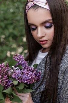 Świeży portret ładna kobieta z seksownymi ustami z kolorowym makijażem w szarym płaszczu z niesamowitymi fioletowymi kwiatami w pobliżu zielonych liści w ogrodzie. wspaniała dziewczyna czarujący patrzy na bukiet bzu. piękna pani ciesz się.