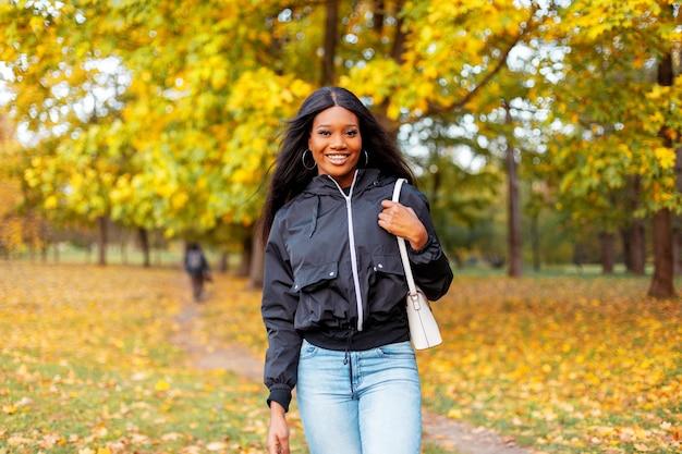 Świeży portret pięknej szczęśliwej młodej czarnej dziewczyny z uśmiechem w modnej casualowej kurtce i dżinsach z torebką spaceruje po jesiennym parku ze złotymi jesiennymi liśćmi