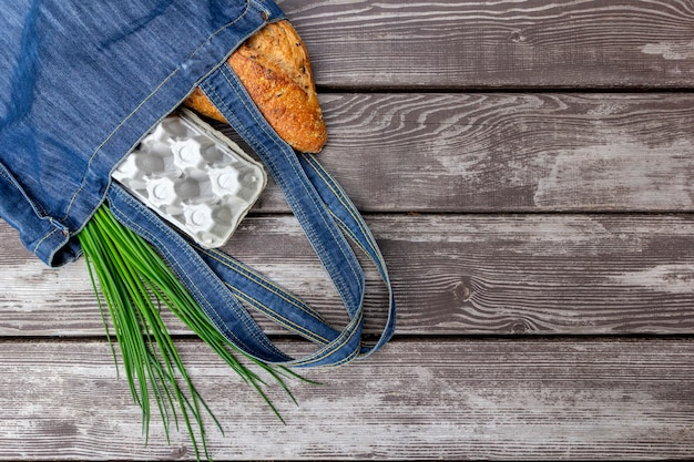 Świeży produkt w torbie rynku na drewnianym stole. przyjazna dla środowiska torba na zakupy wielokrotnego użytku.