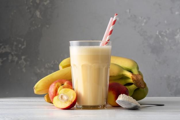 Świeży proteinowy shake z nektaryną lub brzoskwinią na białym drewnianym stole. świeży morelowy koktajl mleczny. szklanka bananowego koktajlu.
