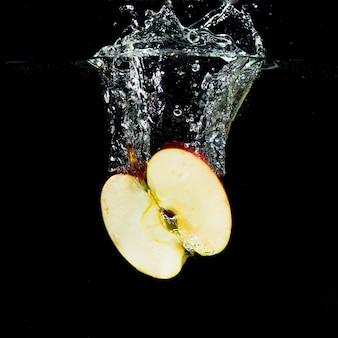 Świeży przekrawający jabłko z wodnym pluśnięciem na czarnym tle