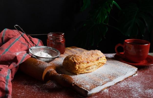 Świeży puff nadziewany dżemem śliwkowym lub z czerwonej porzeczki na stole z czerwoną filiżanką i słoikiem dżemu