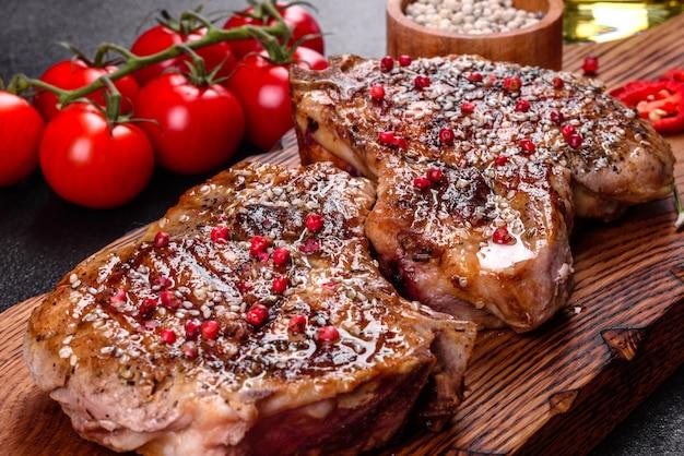 Świeży pyszny soczysty stek na kości z warzywami i przyprawami. soczysty stek wieprzowy grill na ciemnym stole