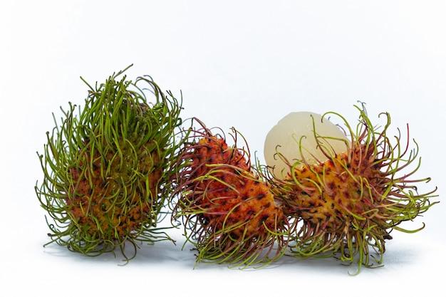 Świeży rambutan izoluje z zielonym liściem. świeży bliźniarka w bambusowym koszu na bielu
