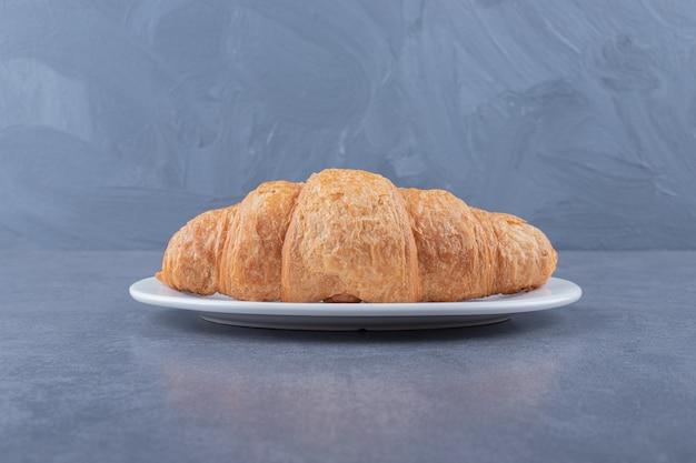 Świeży rogalik francuski na białym talerzu.