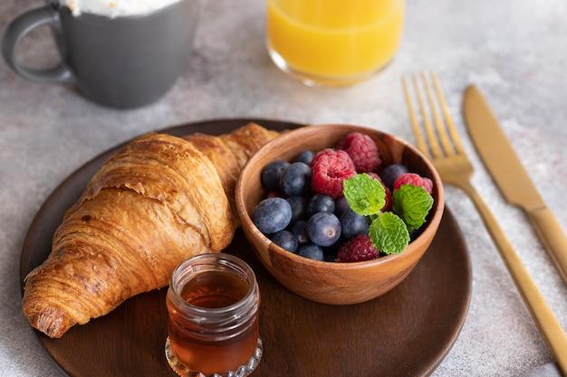 Świeży rogalik, kawa z mlekiem, jagody, syrop i sok pomarańczowy.