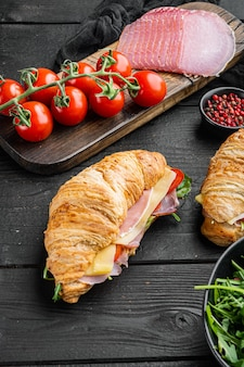 Świeży rogalik lub kanapka z sałatką, szynką, szynką, zestawem prosciutto, ziołami i składnikami, na tle czarnego drewnianego stołu