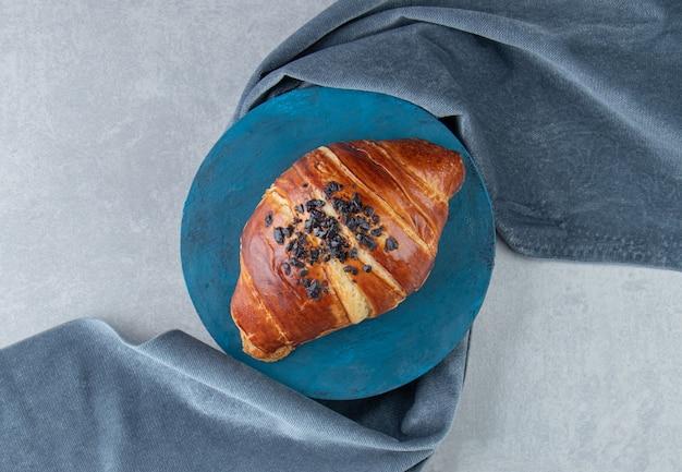 Świeży rogalik ozdobiony kroplą czekolady na niebieskiej desce.