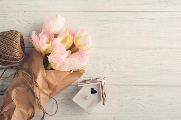 Świeży różowy tulipan, sznurek i ptak dom
