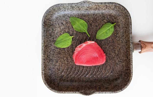 Świeży różowy tuńczyk leży na patelni grillowej, zbliżenie