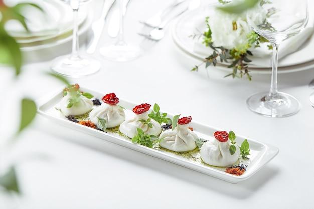 Świeży ser burata z pomidorami i ziołami na białym talerzu