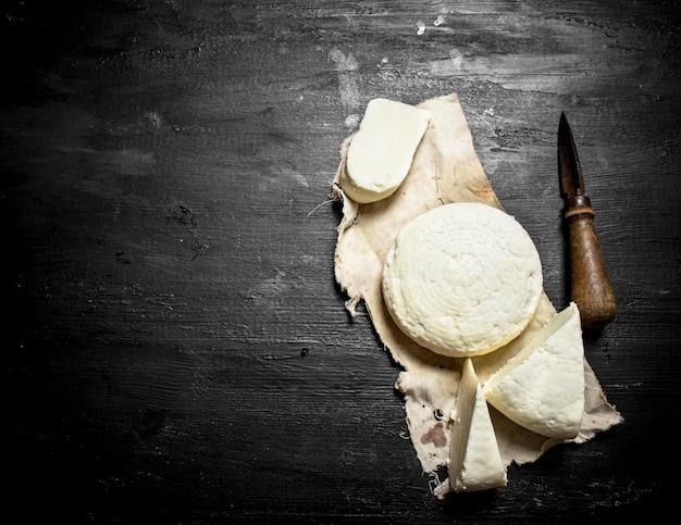 Świeży ser kozi ze starym nożem