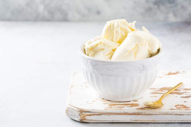 Świeży ser mascarpone w białej misce do przygotowania włoskiego deseru tiramisu na jasnym tle. selektywna ostrość.