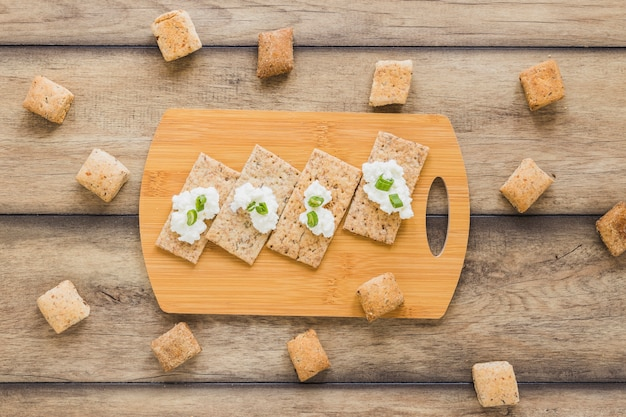 Świeży ser śmietankowy na chrupiącym chlebie nad deską do krojenia na biurku