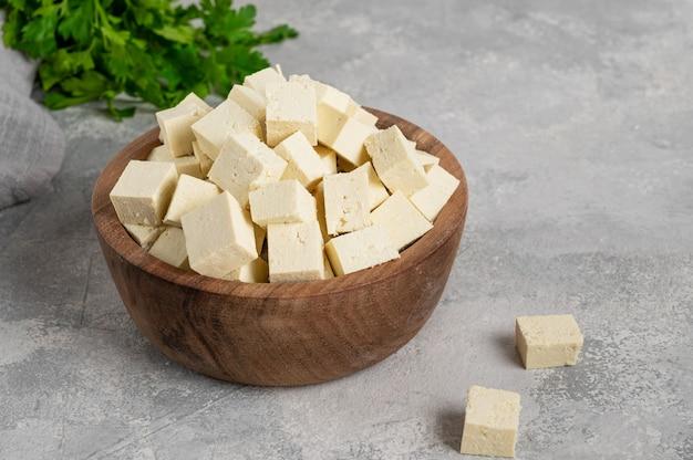 Świeży ser tofu z kostek sojowych z pietruszką na drewnianej misce na szarym tle