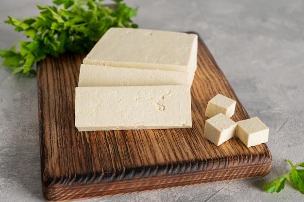 Świeży ser tofu z soi z natką pietruszki na drewnianej desce do krojenia