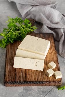 Świeży ser tofu z soi z pietruszką na desce na szarym tle. produkt wegański.