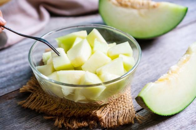 Świeży słodki melon zielony w szklanej misce na tle drewniany stół. koncepcja owoców. ścieśniać