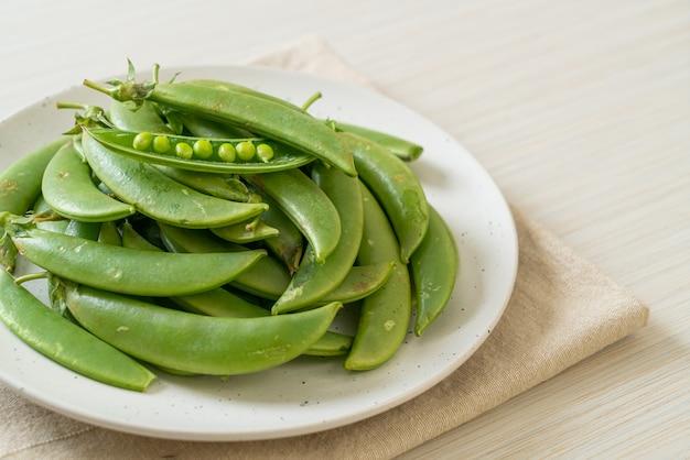 Świeży słodki zielony groszek na białym talerzu