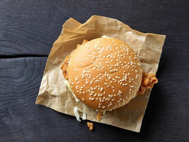 Świeży, smaczny burger na czarnym drewnianym stole, widok z góry