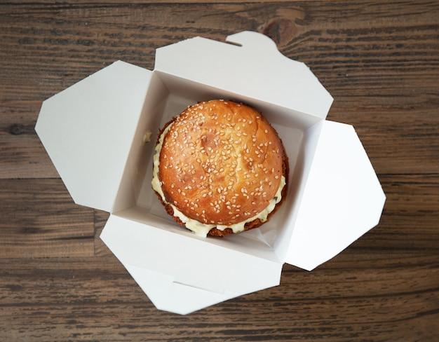 Świeży, smaczny burger w papierowym pudełku na drewnianym stole, widok z góry, selektywne skupienie