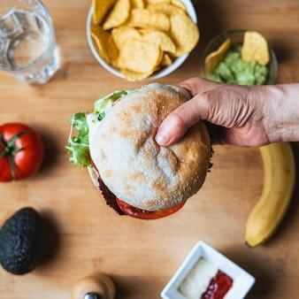 Świeży, Smaczny Burger Z Rustykalną Bułką, Otoczony Nachosami Z Guacamole Do Zanurzania, Szklanką Wody, Pomidorem, Awokado, Papryką, Keczupem I Majonezem Oraz Bananem. Premium Zdjęcia