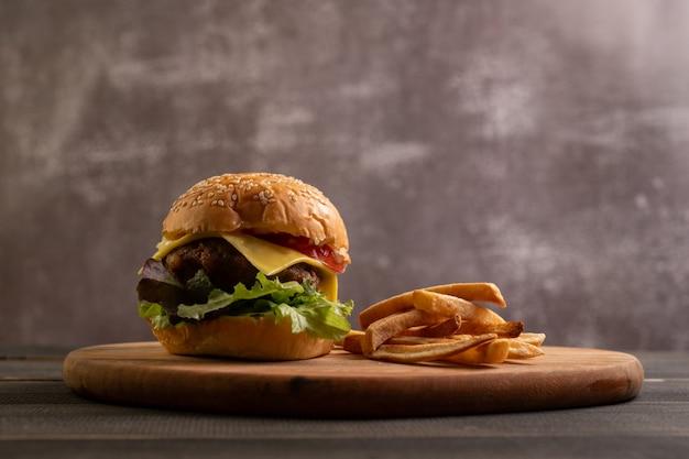 Świeży smaczny domowy hamburger ze świeżymi warzywami na desce do krojenia z frytkami.