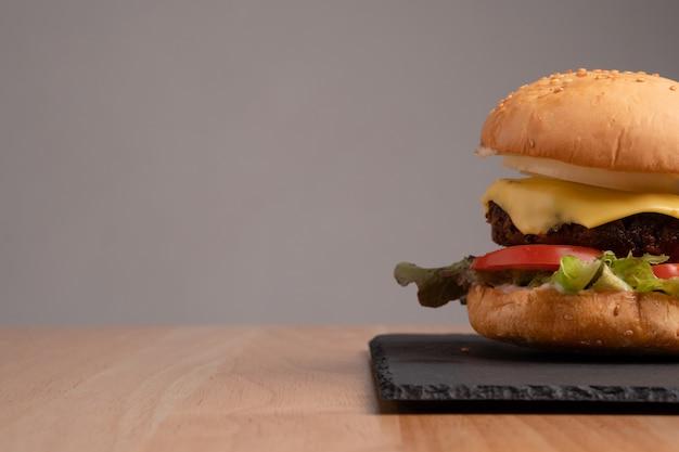 Świeży smaczny domowy hamburger ze świeżymi warzywami, sałatą, pomidorem, serem na desce do krojenia.