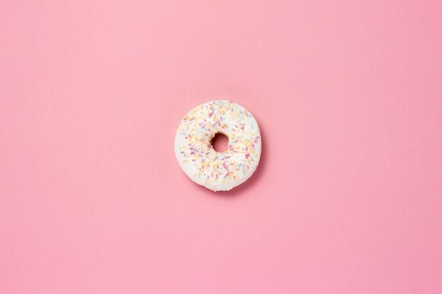 Świeży smakowity słodki pączek na różowym tle. pojęcie fast food, piekarnia, śniadanie, słodycze. minimalizm. leżał płasko, widok z góry.