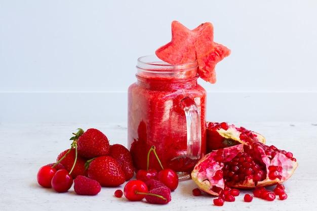 Świeży smoothy czerwony zdrowy napój w szklanych słoikach ze składnikami
