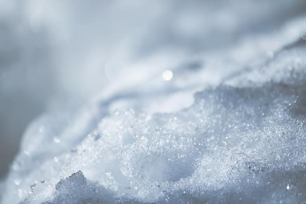 Świeży śnieg i przezroczysta powierzchnia lodu w słoneczny zimowy dzień.