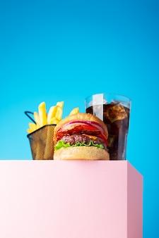 Świeży soczysty hamburger wołowy, cola i smażone frytki umieszczone na różowej podstawce i niebieskim tle. skopiuj miejsce na tekst, modny widok bohatera