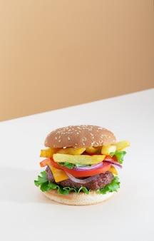 Świeży soczysty hamburger wołowy umieszczony na kreatywnym beżowym tle z przestrzenią do kopiowania, izometryczna orientacja pionowa