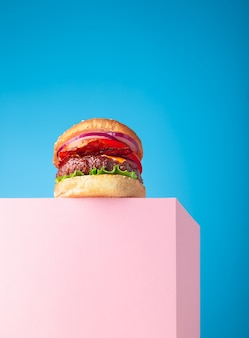 Świeży soczysty hamburger wołowy umieszczony na różowej podstawce i niebieskim tle. skopiuj miejsce na tekst, modny widok bohatera