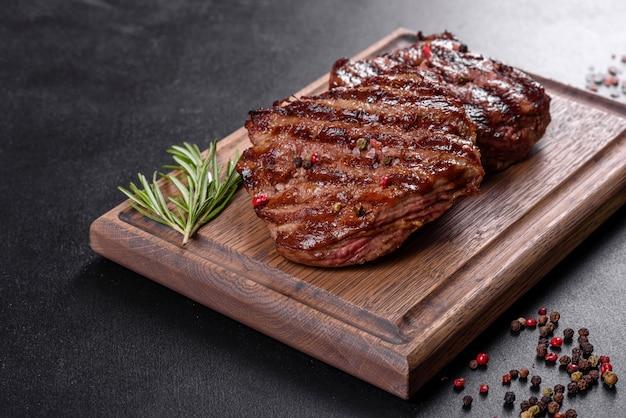 Świeży soczysty pyszny stek wołowy na ciemnej powierzchni. danie mięsne z przyprawami i ziołami