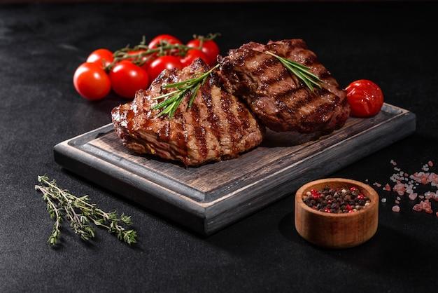 Świeży soczysty pyszny stek wołowy na ciemnym stole. danie mięsne z przyprawami i ziołami
