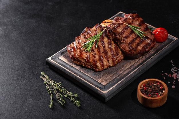 Świeży soczysty pyszny stek wołowy na czarnej tablicy. danie mięsne z przyprawami i ziołami