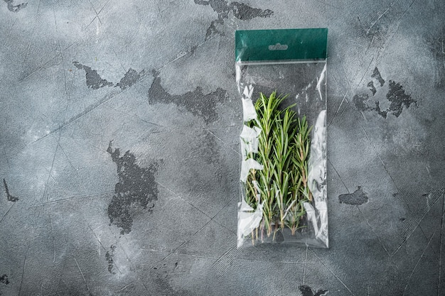 Świeży soczysty rozmaryn w zestawie market pack, na szarym tle, płaski widok z góry, z copyspace i miejscem na tekst